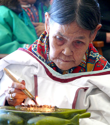 Elder Regeelie Paneak lights a qulliq during the official opening of the Piqqusilirivvik cultural school in Clyde River May 4. The school will open its doors to students in September. (PHOTO COURTESY OF CLEY)