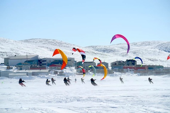 Kite-skiers speed in front of the sea ice in Kangiqsujuaq where the Nunavik kite-ski championship took place earlier this month. (PHOTO BY GEORGE ANAUTAQ PIRLUTUUT)