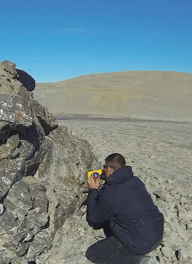 Jeremy Hansen checks out some rocks on Devon Island during his trip to Nunavut in July. His goal: to hone his geological skills so that one day he can go to the moon or even Mars. (PHOTO COURTESY OF FLICKR/ CANADIAN SPACE AGENCY)