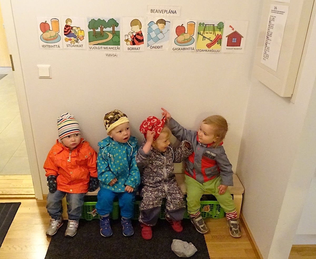 In the Máttabiegga Giellabeassi (South Wind Language Nest) in Helsinki, Finland, a group of Saami tots sit under diagrams in Saami which show their regular day schedule, or Beaveplána. (PHOTO BY JANE GEORGE)
