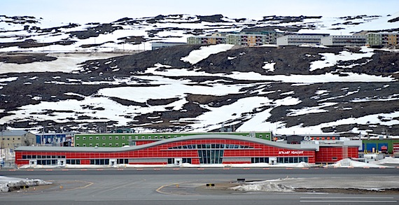 The shallow curved roof of the new Iqaluit air terminal, as seen from across the runway, is engineered to prevent snowdrift accumulation. Tall windows facing south let natural light shine deep into the terminal. The terminal's red colour, in keeping with the colours of other buildings in the city, makes it stand out. In September 2015 a tar fire on the unfinished roof sent large plumes of black smoke billowing up and caused about $1-million in damages. While the fire didn't end up slowing down completion of the terminal, John Hawkins, the Government of Nunavut's airport director, says the fire stands out as the