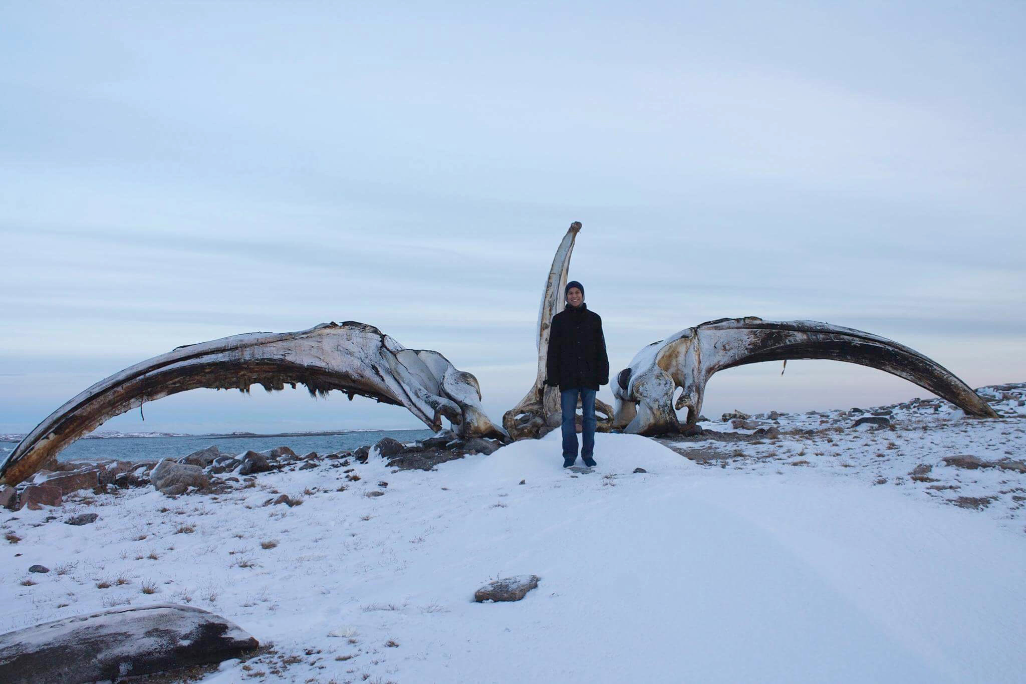 Alex Angnaluak stands in front of a bowhead whale jaw on a visit to Naujaat last year. (HANDOUT PHOTO)